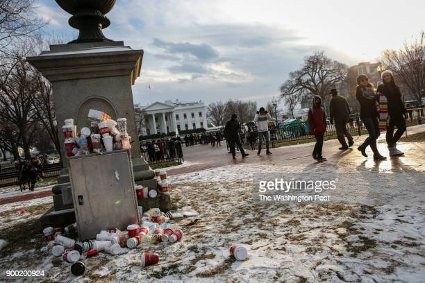 A collection of coffee cups lie piled up on Lafayette Park by visitors as they walk to see the White House during a cold afternoon in Washington DC...
