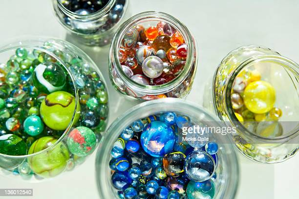 collection of colorful marbles in jars