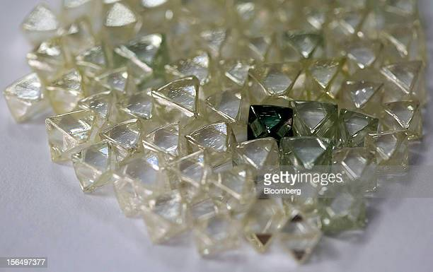 A collection of colorless and colored uncut diamonds sit on a sorting table at DTC Botswana a unit of De Beers in Gaborone Botswana on Thursday Oct...