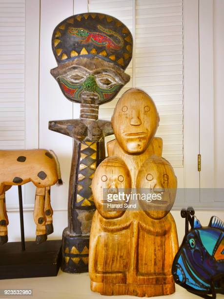 Collection of decorated handmade carved wood objects, fertility doll, triplet doll, painted fish bowl, souvenirs.