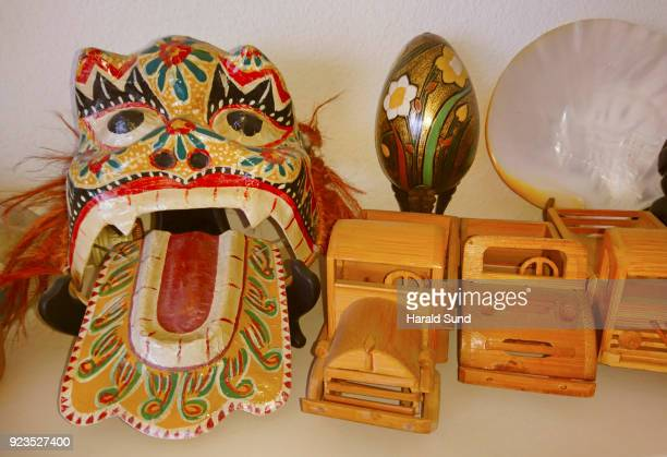 Collection of decorated handmade wood objects, cars, painted egg, seashell and souvenirs.