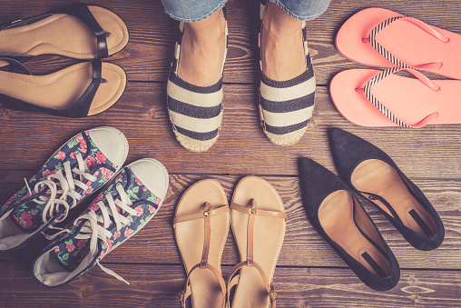 Collection of female shoes on wooden floor. 670069378