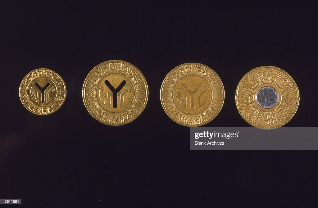 A collection of four New York subway tokens, undated. (L-R) Small cut-out Y, used from 1953-1970; large cut-out Y, used from 1970-1980; engraved Y, used from 1980-1986; filled circle, used from 1986-1995.