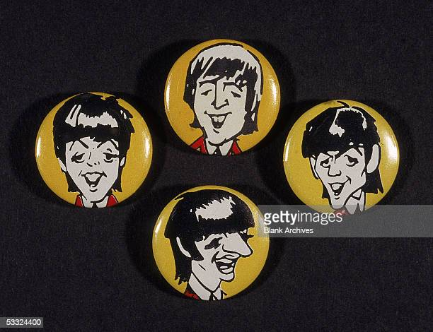 Collection of four pinbacked buttons which feature cartoon renditions of each member of the British pop group the Beatles on a yellow background...