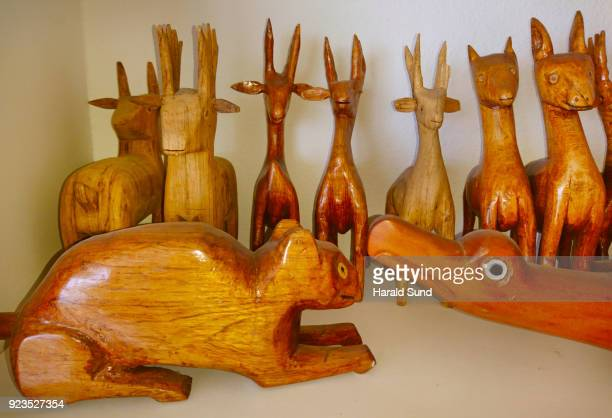 Collection of hand made carved wood lamas, bird and an animal figure displayed on a shelf.