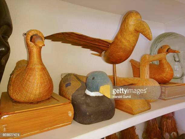 Collection of hand made decorated carved wood birds and ducks displayed on a shelf.