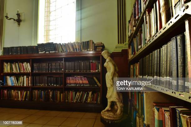 A collection of hardcovered1980's book sets sit in shelves in a hall adorned with a victorian statuette inside the colonialera McMillan Memorial...