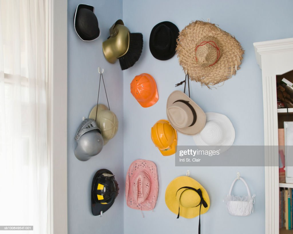 Collection of hats hanging on wall indoors : Stock Photo