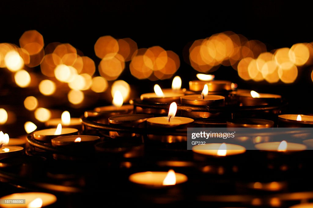 A collection of lit prayer candles against a dark backdrop : Stock Photo