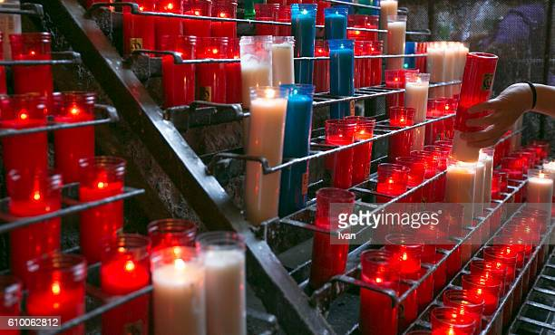 A collection of lit prayer candles in a church