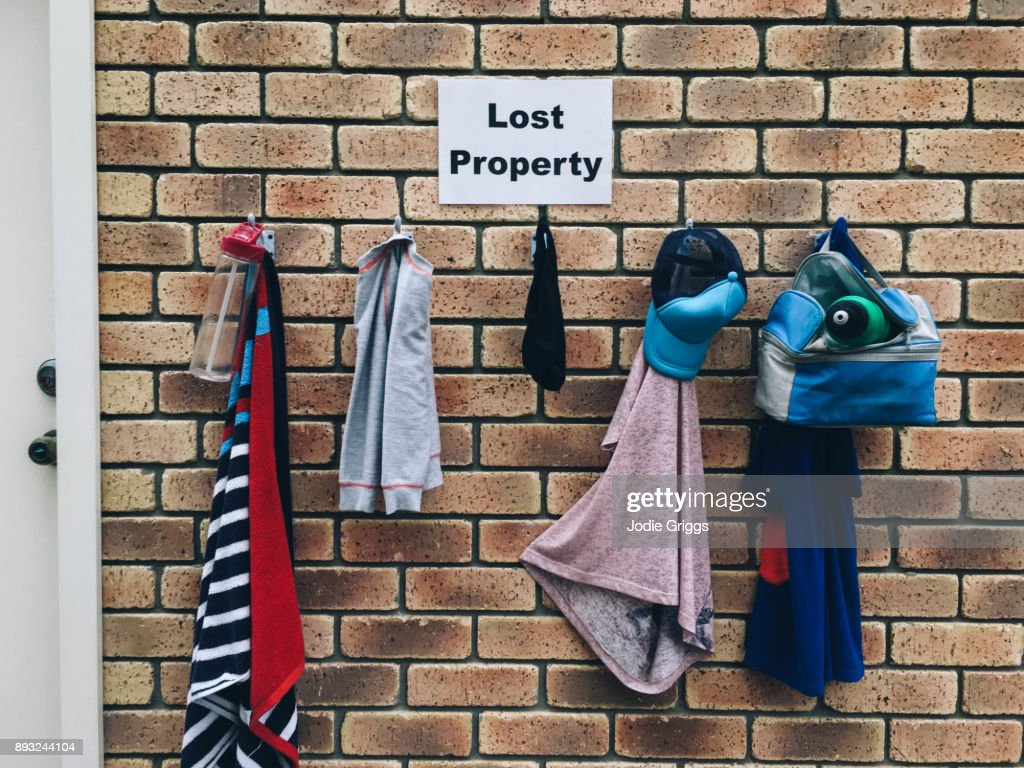 A Collection Of Lost Property Hanging On Hooks Against A Brick Wall