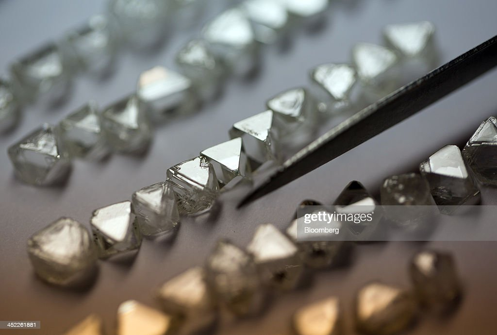 A collection of natural diamonds are seen laid in rows on a sorting table before the productions process at OAO Alrosa's cutting and polishing unit, Brilliantly Alrosa, in Moscow, Russia, on Tuesday, Nov. 26, 2013. OAO Alrosa, Russia's diamond producer, raised about $1.3 billion in an oversubscribed share sale from investors including Oppenheimer Funds Inc. and Lazard Ltd.'s asset-management, as part of a state strategy to attract more international investors to Russia and establish Moscow as a global financial center. Photographer: Andrey Rudakov/Bloomberg via Getty Images
