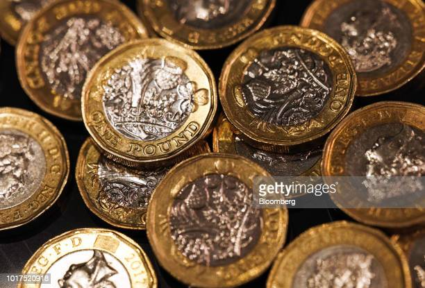 A collection of one pound sterling coins sit in this arranged photograph in London UK on Wednesday Aug 15 2018 The pound's weakness is turning...