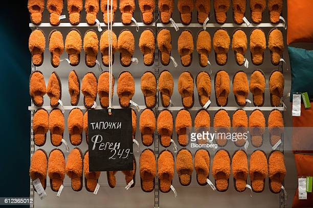 A collection of orange house slippers hang from a display beside a ruble price sign in the Ikea AB retail store in Khimki Russia on Monday Oct 3 2016...