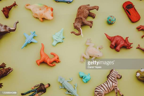 collection of plastic and rubber toys on yellow surface.top view. - grote groep dingen stockfoto's en -beelden