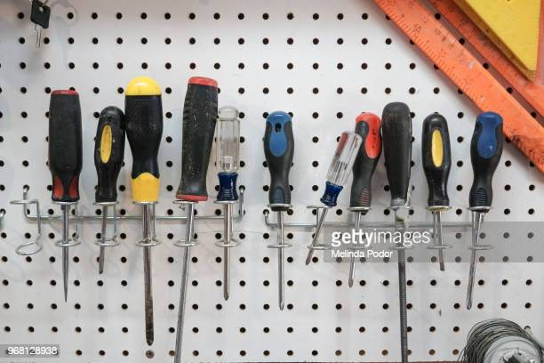 a collection of screwdrivers hanging from a pegboard - schraubenzieher stock-fotos und bilder