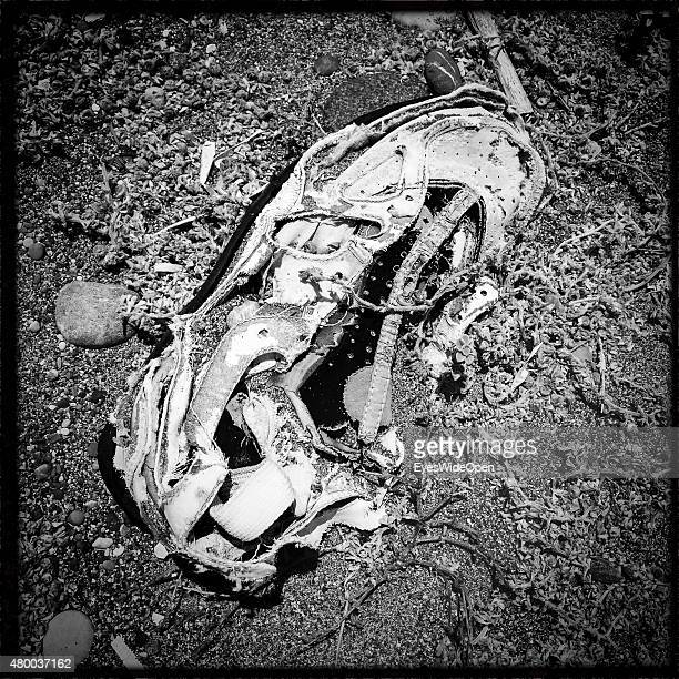 Collection of shoes as flotsam and jetsam on the beach on June 28 2015 in Kattavia Rhodes Dodecanes Greece