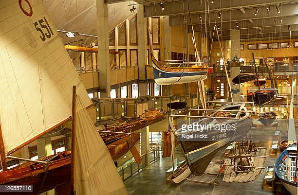 collection of small boats on display inside the main exhibition hall at the national maritime museum cornwall - ファルマス ストックフォトと画像
