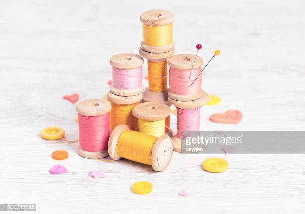 collection of spools threads pins in yellow pink colors arranged on a white wooden background - embroidery stock pictures, royalty-free photos & images