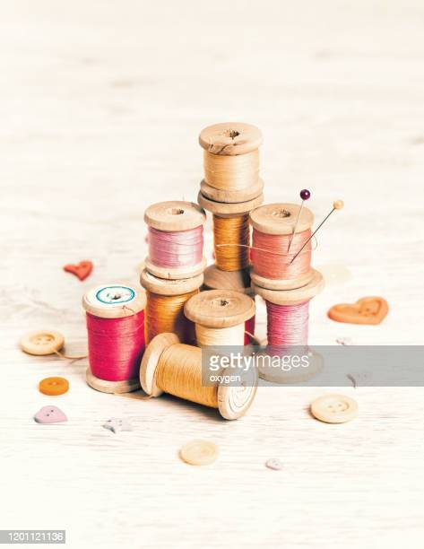 collection of spools threads pins in yellow pink colors arranged on a white wooden background - button sewing item stock pictures, royalty-free photos & images