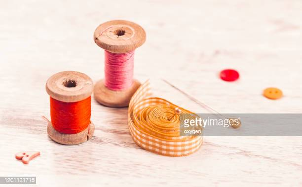 collection of spools threads pins in yellow pink colors arranged on a white wooden background - ribbon sewing item stock pictures, royalty-free photos & images