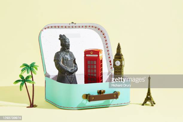 a collection of travel souvenirs emerging from a suitcase - richard drury stock pictures, royalty-free photos & images