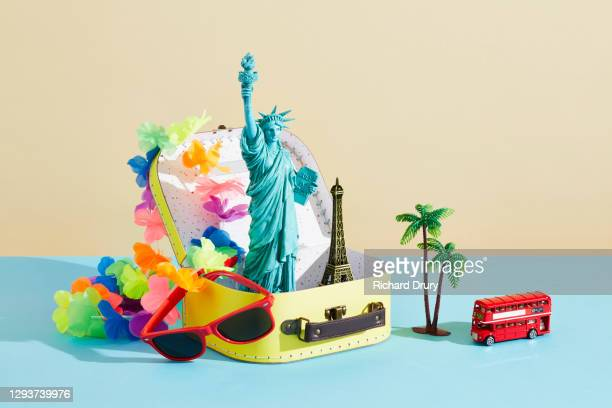 a collection of travel souvenirs in and around a suitcase - suitcase stock pictures, royalty-free photos & images