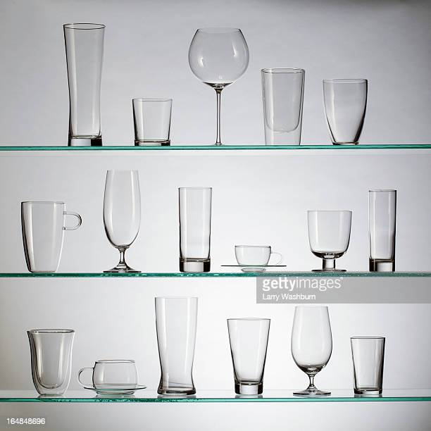 A collection of various types of drinking glasses arranged neatly on three shelves