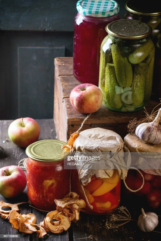 Collection set of many homemade glass jars with preserved food (cucumbers, tomatoes, peppers), with garlic and fresh and dried apples. Over old wooden table. Dark rustic style : News Photo