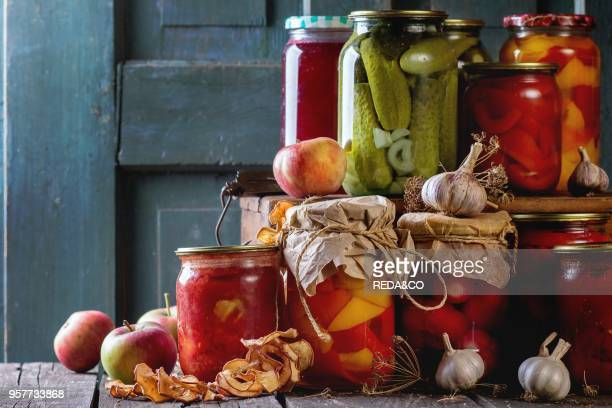 Collection set of many homemade glass jars with preserved food with garlic and fresh and dried apples Over old wooden table Dark rustic style