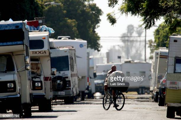A collector of recyclable cans and bottles rides a bike down W 94th Street near LAX in an area that had become a community of homeless people living...