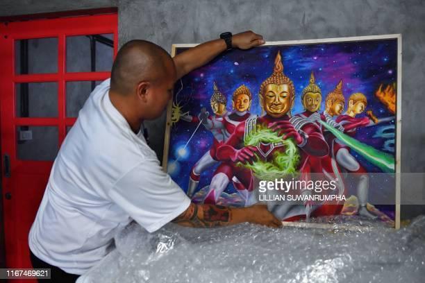 Collector Pakorn Porncheewangkul arranges a painting depicting Buddha as Japanese superhero Ultraman in his home in Bangkok on September 12, 2019. -...