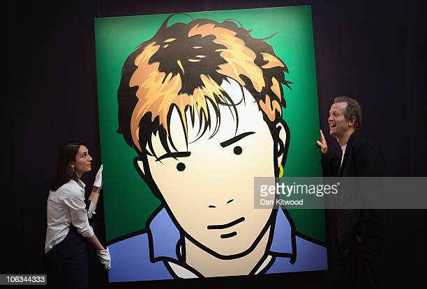 Collector Robert Devereux helps a Sotheby's employee hang a piece of artwork by British artist Julian Opie depicting an image of Blur frontman Damon...