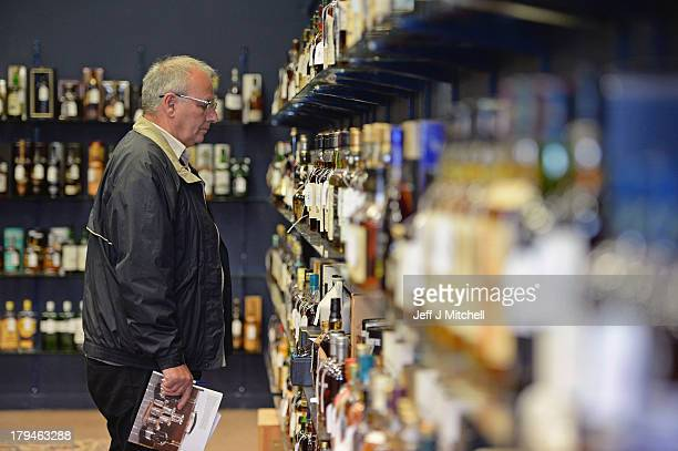 A collector views whiskies going on sale today at McTears Auctioneers on September 4 2013 in Glasgow Scotland Whiskey collectors as far afield as the...