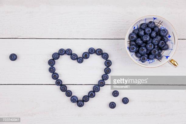 Collectors cup of blueberries and heart shaped with blueberries on wood
