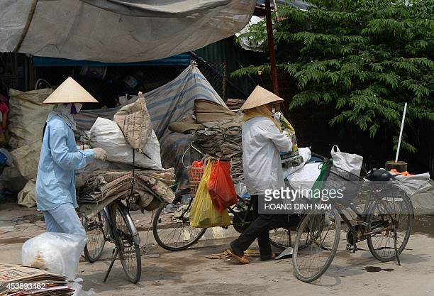Collectors of recyclable items arrive on bicycles to sell what they collected at a trader's buying point set up near the Keanang buildings Vietnam's...
