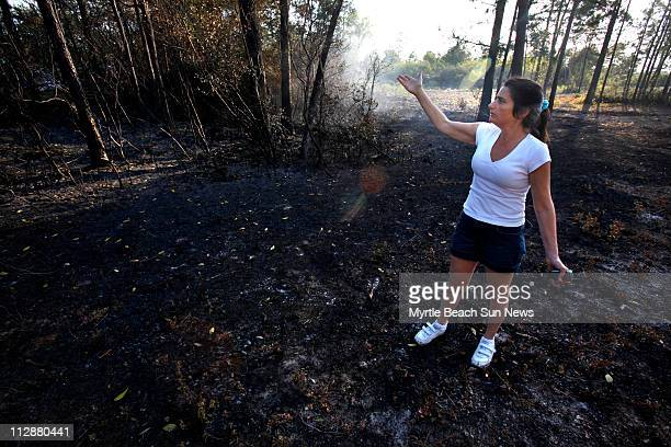 Colleen Bury stands at the rear of her property on Friday April 24 adjacent to Mark Torchi's property where officials say the wildfire started...