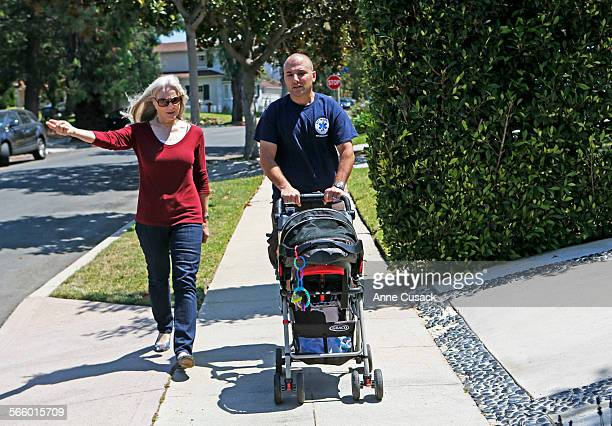 Colleen Mason and Greg Spiegelman with his baby Drew walk the streets of their neighborhood in Cheviot Hills in Los Angeles on July 24 2013 they are...