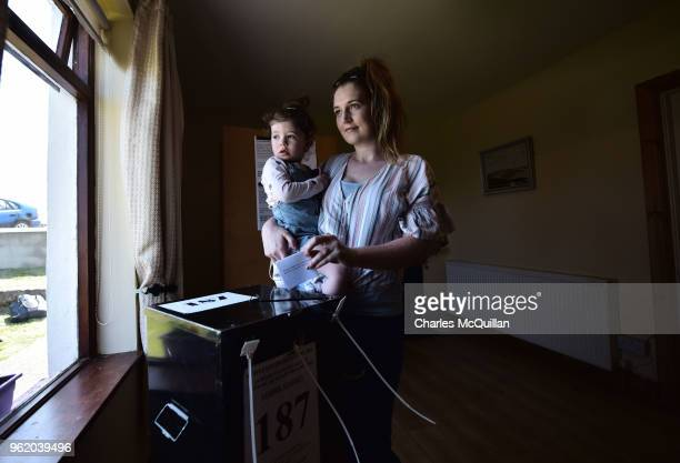 Colleen Ui Fhroruisce casts her vote as she holds her daughter Saoirse as voting takes place a day earlier than the main land on May 24 2018 in Gola...