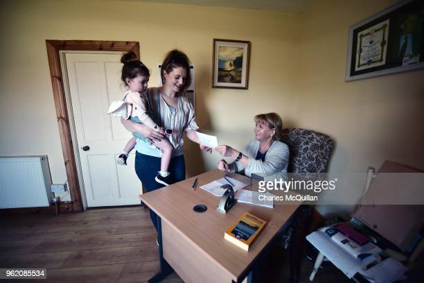 Colleen Ui Fhroruisce holds her daughter Saoirse as she receives her ballot card from presiding officer Nancy Sharkey as voting takes place a day...