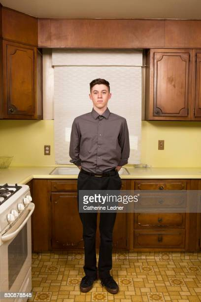 college age boy standing straight and tall for portrait in grandmother's empty kitchen - monrovia california stock pictures, royalty-free photos & images