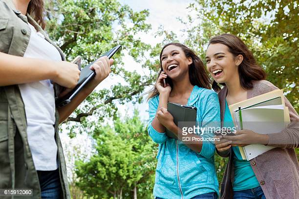 College age friends laughing and using smartphones on campus
