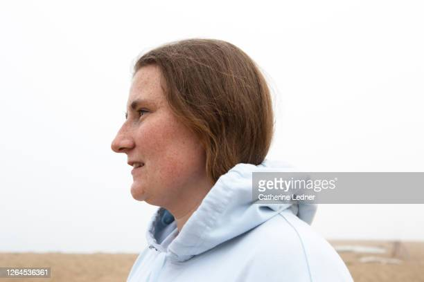 college aged girl in profile at the beach on a foggy day - catherine ledner stock pictures, royalty-free photos & images