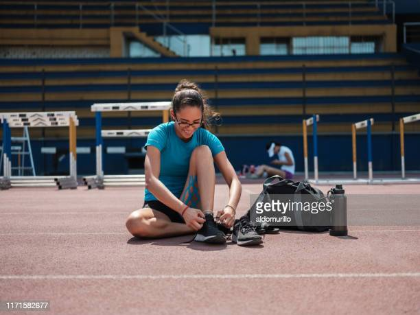 college athlete tying running shoes - gym bag stock pictures, royalty-free photos & images