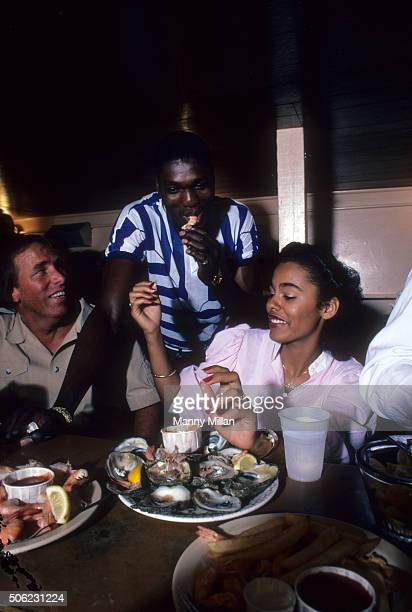 Casual portrait of Houston center Akeem Olajuwon with his girlfriend Lita Spencer and Chris Pond during photo shoot on UH campus Pond had coached...