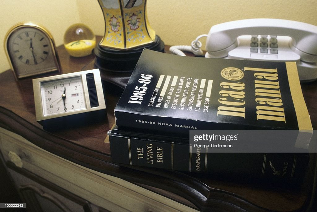 Closeup of LSU coach Dale Brown's two alarm clocks with NCAA manual and bible on dresser at home. Baton Rouge, LA 9/20/1985