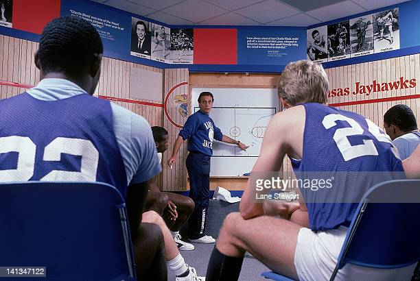 Kansas head coach Larry Brown in locker room with players designing plays on board during practice Lawrence KS CREDIT Lane Stewart