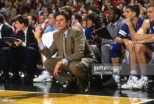 Kentucky coach Rick Pitino squatting in front of bench during game vs Louisville at Freedom Hall View of Kentucky assistant coaches Bernadette Locke...
