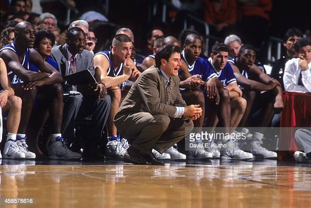 Kentucky coach Rick Pitino squatting in front of bench during game vs Louisville at Freedom Hall View of Kentucky assistant coach Bernadette Locke in...