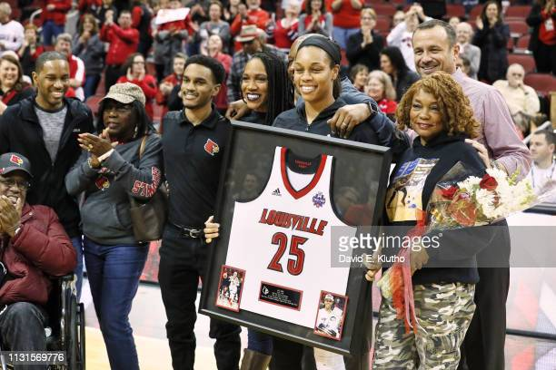 Louisville Asia Durr holding her framed jersey during ceremony on court on Senior Day before game vs North Carolina State at KFC Yum Center...